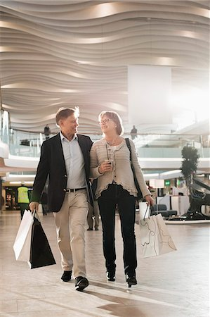 shopping mall - Happy senior couple with bags walking in shopping mall Stock Photo - Premium Royalty-Free, Code: 698-06616200