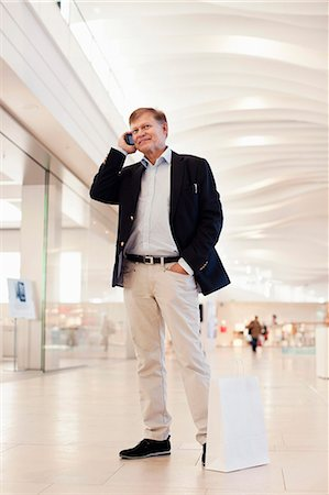 shopping mall - Full length of happy senior man with shopping bag using cell phone in mall Stock Photo - Premium Royalty-Free, Code: 698-06616216