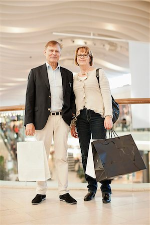 Full length of happy senior couple carrying bags in shopping mall Stock Photo - Premium Royalty-Free, Code: 698-06616212