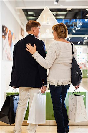 Rear view of senior couple with bags looking in store window at mall Stock Photo - Premium Royalty-Free, Code: 698-06616221