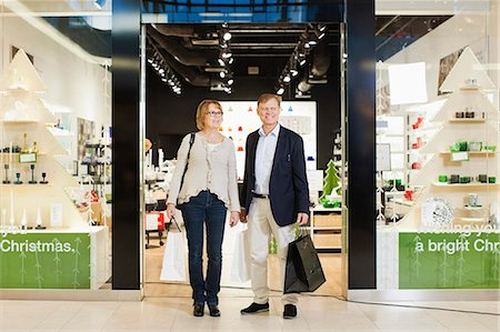 shopping mall - Full length of happy senior couple with shopping bags standing in front of store Stock Photo - Premium Royalty-Free, Code: 698-06616223