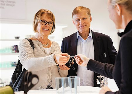 sold sign - Happy senior couple handing over credit card to saleswoman in store Stock Photo - Premium Royalty-Free, Code: 698-06616234
