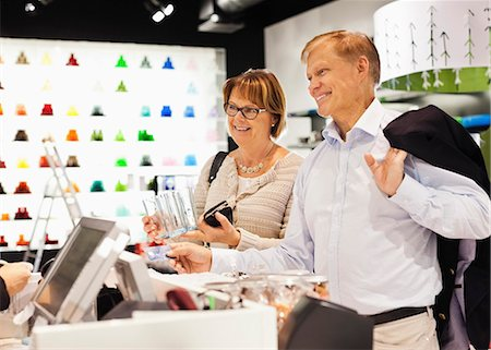 sold sign - Happy senior couple handing over credit card to saleswoman in store Stock Photo - Premium Royalty-Free, Code: 698-06616235