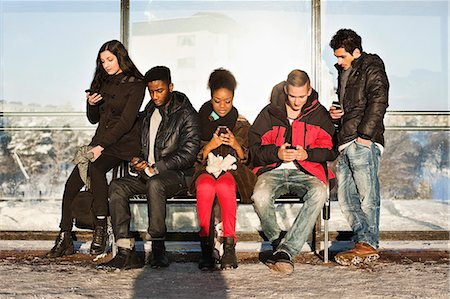 Group of multi ethnic friends using mobile phones on bench Stock Photo - Premium Royalty-Free, Code: 698-06616244