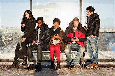 Portrait of young woman with multi ethnic friends using mobile phones on bench Stock Photo - Premium Royalty-Free, Code: 698-06616245