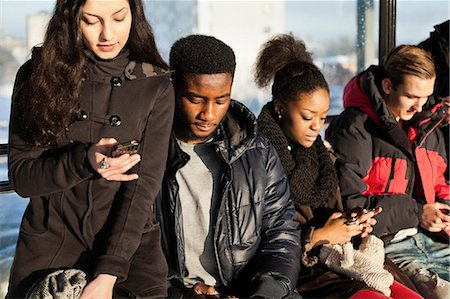Group of multi ethnic friends using mobile phones Stock Photo - Premium Royalty-Free, Code: 698-06616246