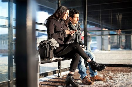 Happy friends in warm clothes holding mobile phones while looking away Stock Photo - Premium Royalty-Free, Code: 698-06616240