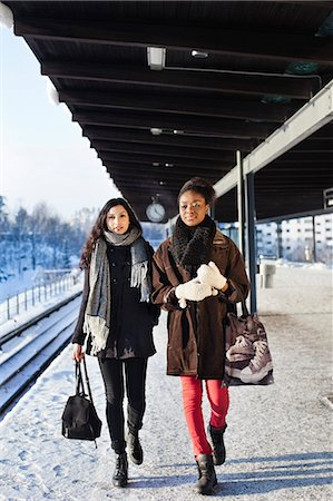 Young female friends in warm clothing walking on station platform Stock Photo - Premium Royalty-Free, Code: 698-06616255