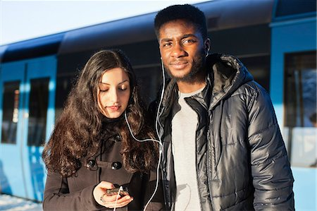 Young friends listening music through hands-free device against train Stock Photo - Premium Royalty-Free, Code: 698-06616253