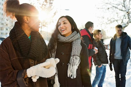 Happy young women in warm clothing with male friends in background Stock Photo - Premium Royalty-Free, Code: 698-06616269