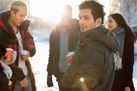 Portrait of young man with friends in warm clothes holding disposable cups Stock Photo - Premium Royalty-Free, Code: 698-06616263