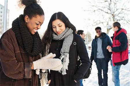Happy young female friends in warm clothing with men in background Stock Photo - Premium Royalty-Free, Code: 698-06616270