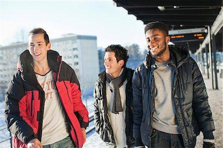 Happy multi ethnic friends walking on platform Stock Photo - Premium Royalty-Free, Code: 698-06616273