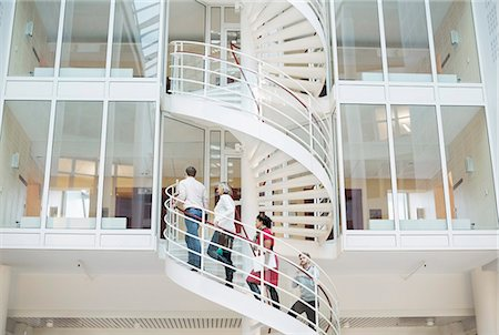 Business people climbing spiral staircase in office Stock Photo - Premium Royalty-Free, Code: 698-06804003