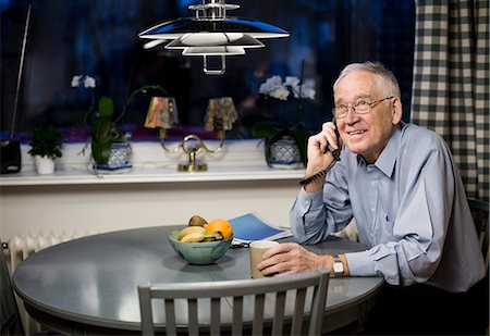 Happy senior looking up while using telephone at dining table Stock Photo - Premium Royalty-Free, Code: 698-06804056