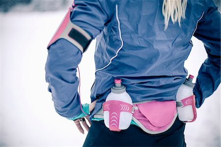 Midsection of woman wearing water bottle belt in winter Stock Photo - Premium Royalty-Free, Code: 698-06804098