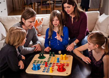 five - Family of five playing ludo together at table Stock Photo - Premium Royalty-Free, Code: 698-06804155