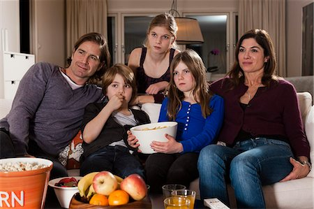 Family of five with bowl of chips watching television in living room Stock Photo - Premium Royalty-Free, Code: 698-06804152