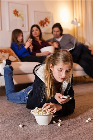Girl using mobile phone while having popcorn on floor with family sitting on sofa in background Stock Photo - Premium Royalty-Free, Code: 698-06804164