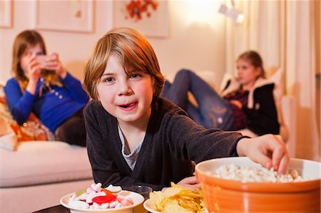 snack - Portrait of little boy eating popcorn at coffee table with sisters in background Stock Photo - Premium Royalty-Free, Code: 698-06804173