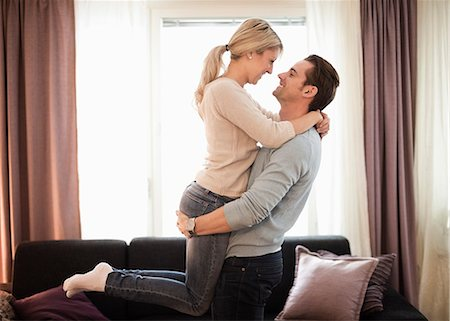Side view of romantic man carrying young woman in living room Stock Photo - Premium Royalty-Free, Code: 698-06804212