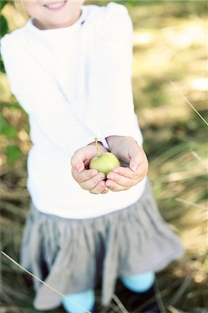 Midsection of little girl holding an apple Stock Photo - Premium Royalty-Free, Code: 698-06804238