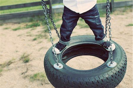 swing (sports) - Low section of little boy standing on tire swing Stock Photo - Premium Royalty-Free, Code: 698-06804241