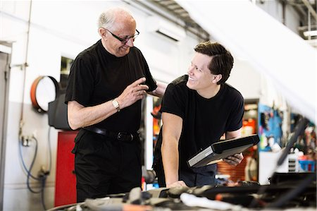 Happy senior male mechanic looking at young coworker at auto repair shop Stock Photo - Premium Royalty-Free, Code: 698-06804279