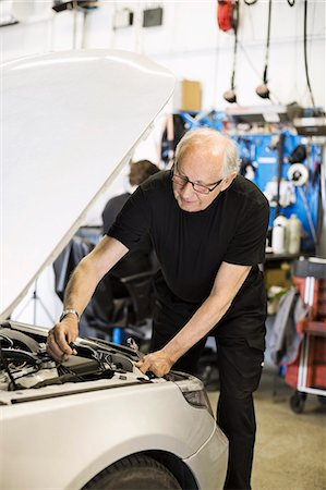 Senior male mechanic working on car engine at auto repair shop with coworker Stock Photo - Premium Royalty-Free, Code: 698-06804270
