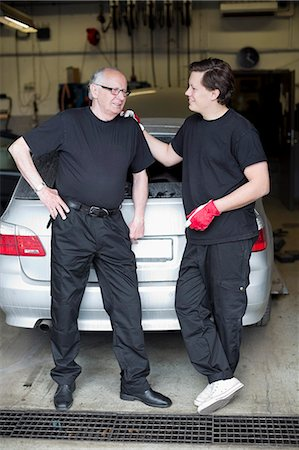 Mechanics discussing while standing against car at auto repair shop Stock Photo - Premium Royalty-Free, Code: 698-06804302