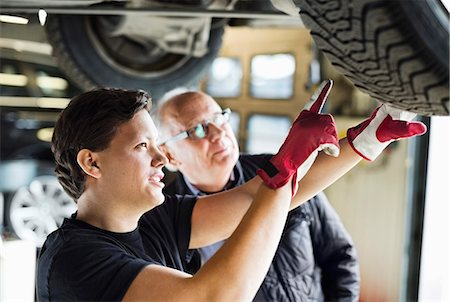 Young mechanic explaining tire problems to customer below car at auto repair shop Stock Photo - Premium Royalty-Free, Code: 698-06804344