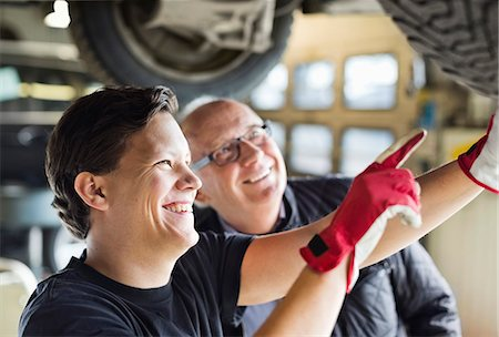 Happy young mechanic explaining tire problems to customer underneath car at auto repair shop Stock Photo - Premium Royalty-Free, Code: 698-06804343
