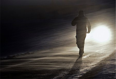 Silhouetted person walking in snowstorm Stock Photo - Premium Royalty-Free, Code: 698-06803984