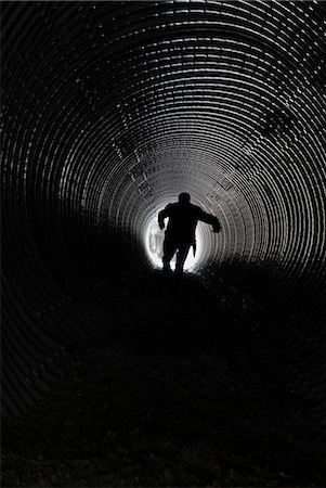Silhouetted person running through tunnel Stock Photo - Premium Royalty-Free, Code: 698-06803987