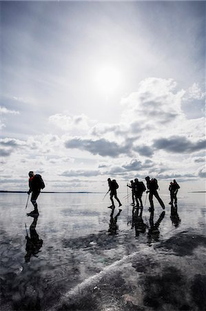 Group of friends walking on frozen lake against cloudy sky Stock Photo - Premium Royalty-Free, Code: 698-06966248