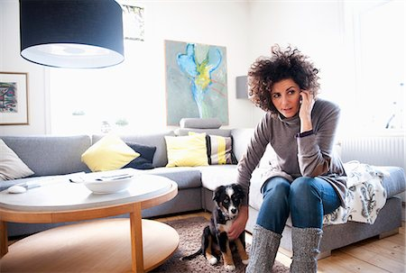 Mature women using mobile phone while sitting with pet dog in living room Stock Photo - Premium Royalty-Free, Code: 698-06966261
