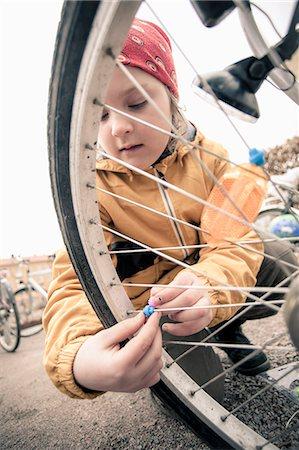Elementary girl fixing beads on bicycle spokes Stock Photo - Premium Royalty-Free, Code: 698-06966319