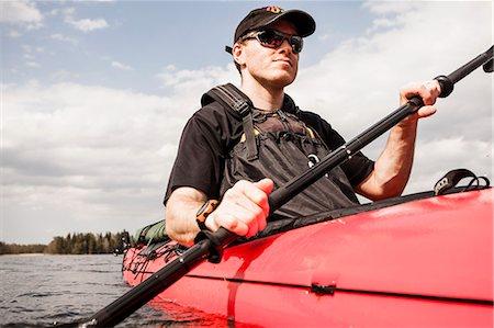 Mid adult man kayaking in lake Stock Photo - Premium Royalty-Free, Code: 698-06966338