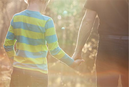 Midsection of boy and father holding hands while standing at park Stock Photo - Premium Royalty-Free, Code: 698-06966332