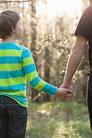 Rear view of boy holding father's hand at park Stock Photo - Premium Royalty-Free, Code: 698-06966333