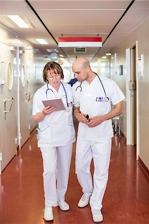 Male and female doctors using digital tablet while walking in hospital corridor Stock Photo - Premium Royalty-Free, Code: 698-06966356