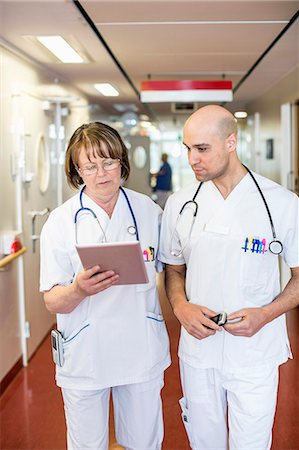Doctors using digital tablet while standing in hospital corridor Stock Photo - Premium Royalty-Free, Code: 698-06966357