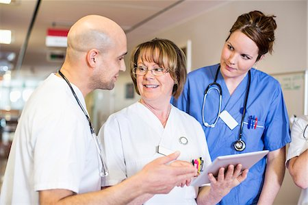 Senior female doctor discussing over digital tablet with colleagues in hospital Stock Photo - Premium Royalty-Free, Code: 698-06966353