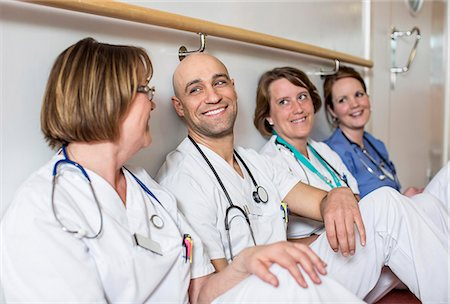 Happy male doctor and female colleagues leaning together on wall in hospital Stock Photo - Premium Royalty-Free, Code: 698-06966365