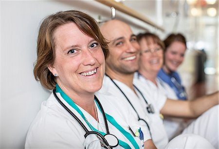 Portrait of happy mature female doctor with colleagues leaning on wall in hospital Stock Photo - Premium Royalty-Free, Code: 698-06966367