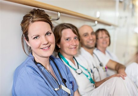 Portrait of beautiful mid adult female doctor with colleagues leaning on wall in hospital Stock Photo - Premium Royalty-Free, Code: 698-06966368