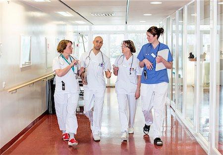Team of doctors communicating while walking in hospital corridor Stock Photo - Premium Royalty-Free, Code: 698-06966362