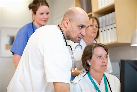 Male and female doctors using computer together in hospital Stock Photo - Premium Royalty-Free, Code: 698-06966377