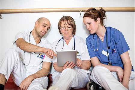 Doctors using digital tablet while leaning on wall in hospital Stock Photo - Premium Royalty-Free, Code: 698-06966370