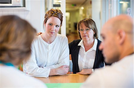 doctor and patient - Mother and daughter getting notice from doctors at table in clinic Stock Photo - Premium Royalty-Free, Code: 698-06966385